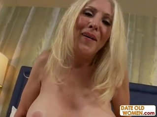 Blonde grandmother on the floor sucking on a cock