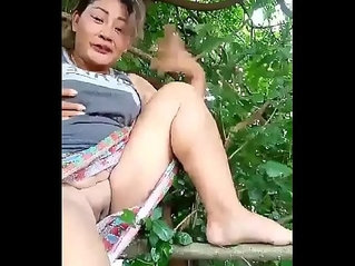 Thai aunty shaved pussy flashing on a tree