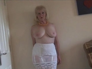 Mature busty lady in stockings and sheer slip strips